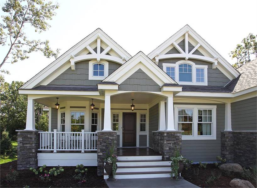 Home entry with covered front porch and stoop framed with stone columns.