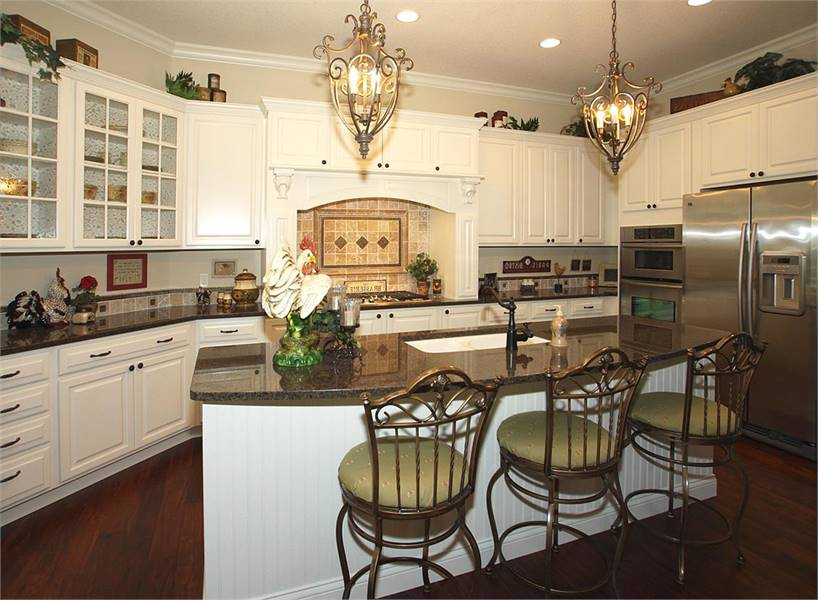The kitchen offers white cabinets, stainless steel appliances, and a beadboard island complemented with round counter stools and ornate pendants.