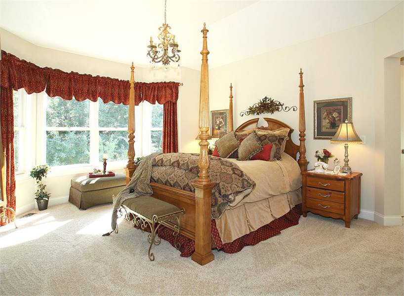 The primary bedroom features a four-poster bed and a sitting area by the bay window dressed in red curtains.
