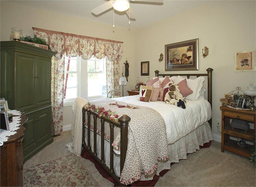 This bedroom has beige walls and a carpet flooring topped by a floral rug.
