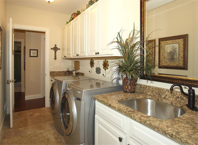 Laundry room with stainless steel appliances, granite top counters, and an undermount sink paired with a wrought iron faucet.