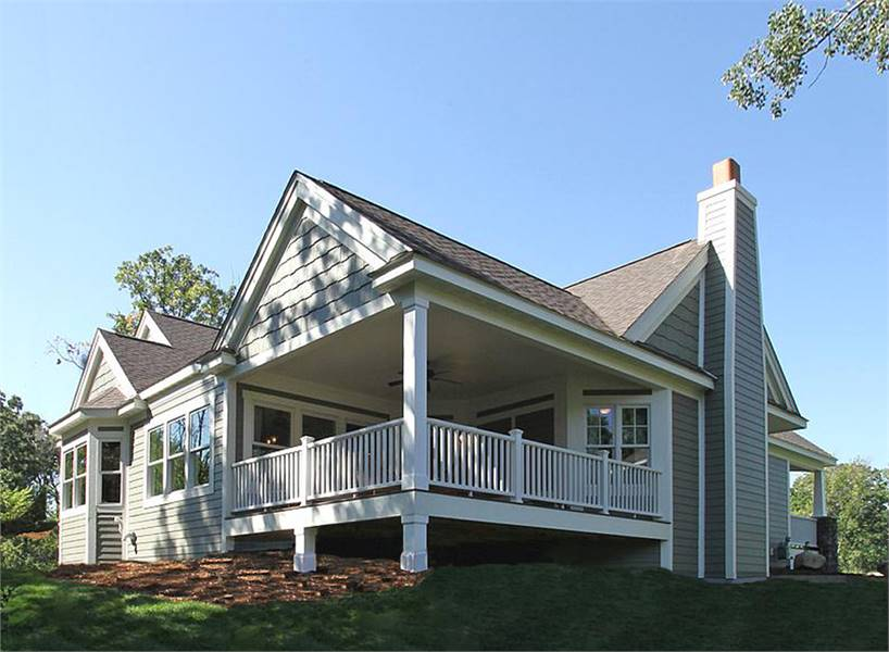 Angled rear exterior view with horizontal siding and a covered porch surrounded with white railings.