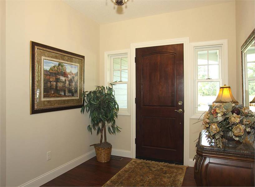 The foyer has a dark wood front door and a vintage rug that lays on the hardwood flooring.