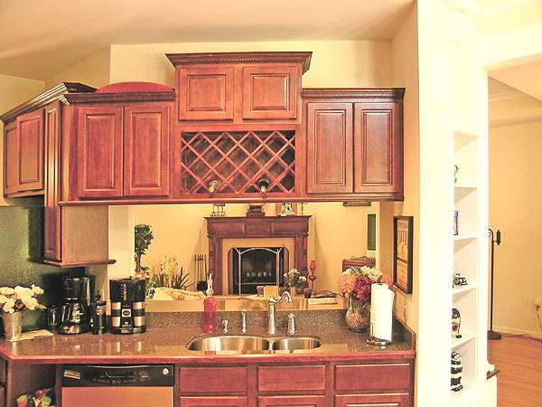 The kitchen is equipped with wooden cabinets, wine shelves, and a double bowl sink fitted on the granite top peninsula.