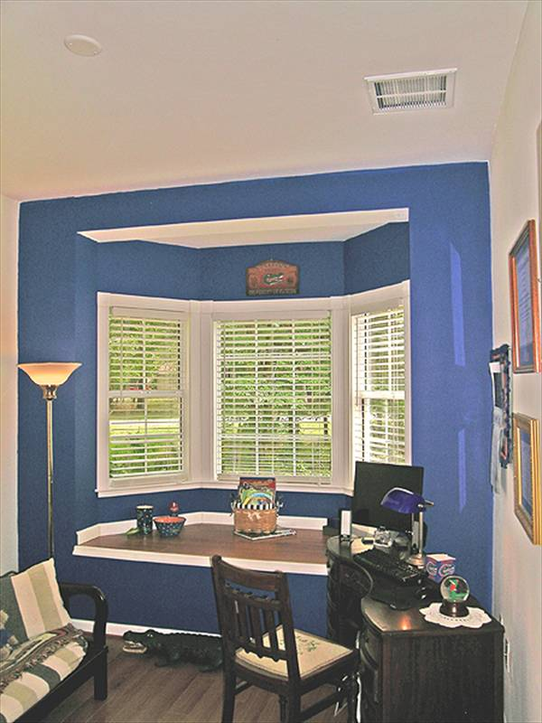 The study offers cushioned chairs, a black desk, and a built-in seat fixed against the bay window.