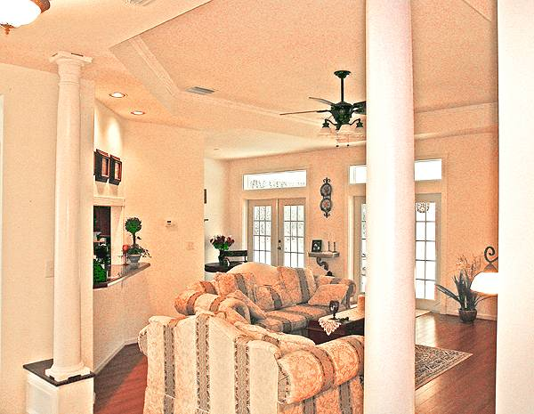 Living room with classy patterned seats and a dark wood coffee table over a printed rug. It is defined with interior columns and a gorgeous step ceiling.