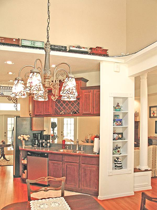 Another view of the kitchen showing the breakfast area with a wooden dining set and an ornate chandelier.