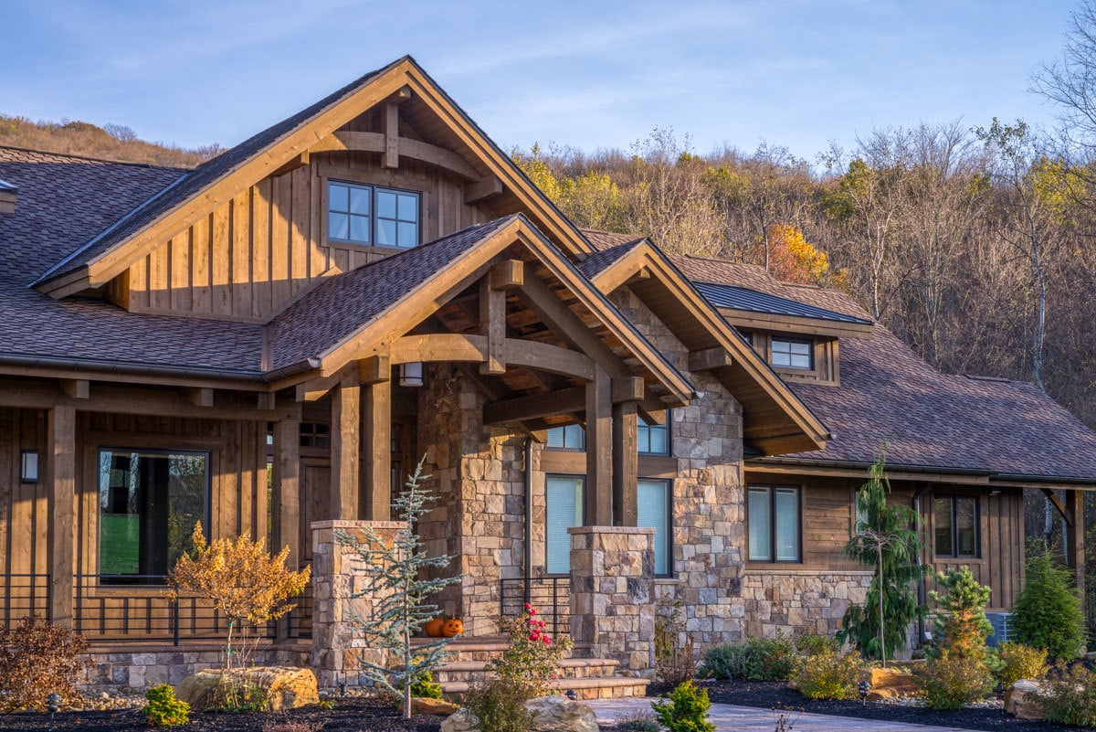 Rustic dark wood trims, stone accents, and gable roofs accentuate the home entry.