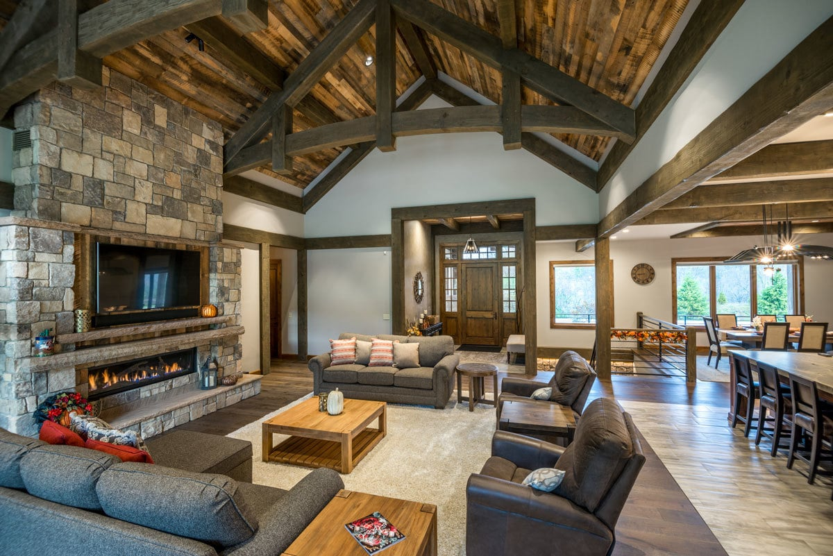 Living room with cozy gray seats, wooden tables, and a stone fireplace with a TV on top.