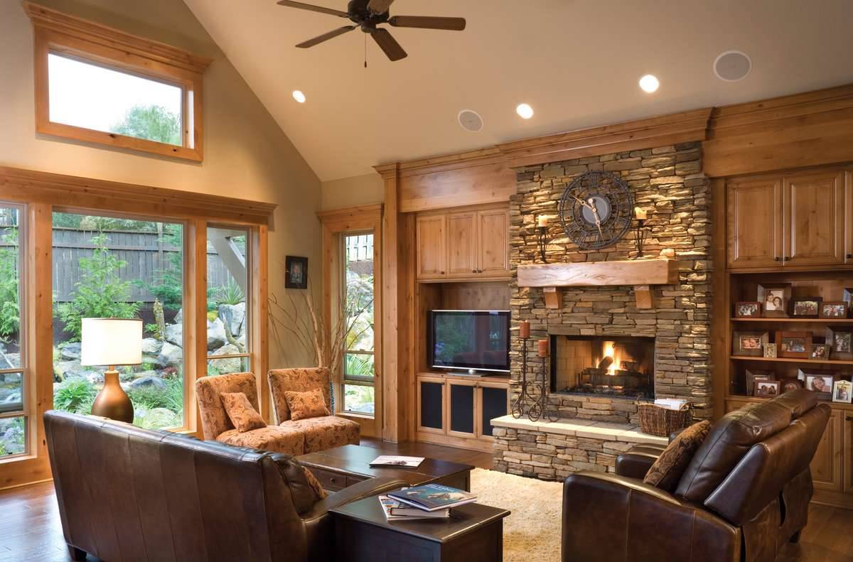The living room has cozy brown seats, a dark wood coffee table, and a stone fireplace flanked with wooden built-ins.