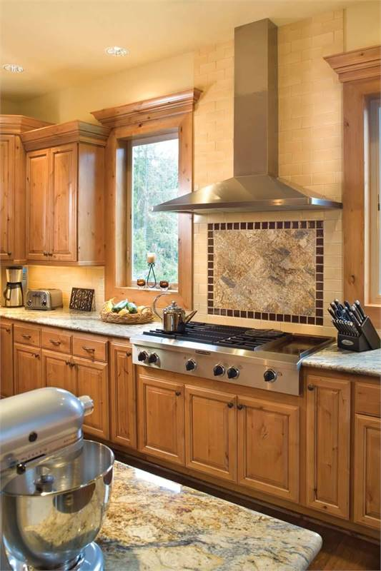 The kitchen is equipped with stainless steel appliances, wooden cabinets, and beige granite countertops.