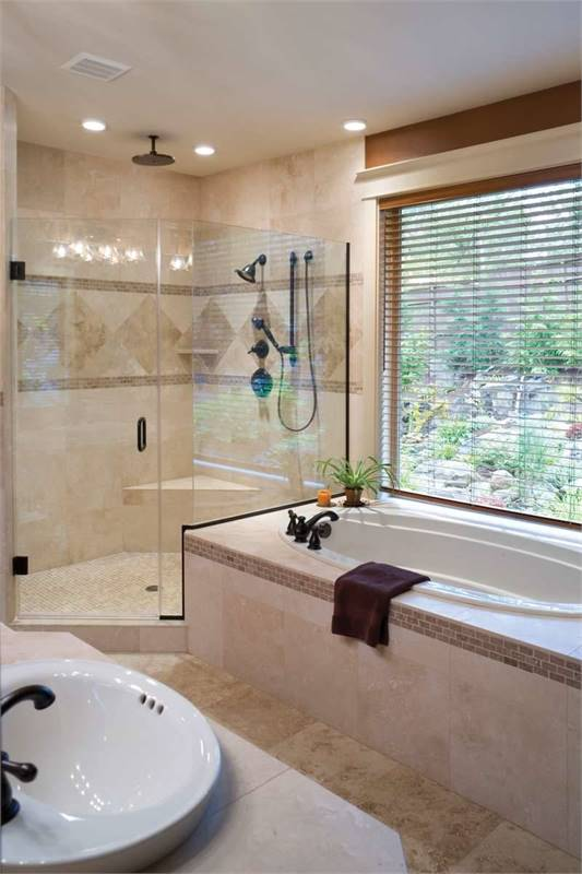 Primary bathroom with a vessel sink vanity, a deep soaking tub, and a walk-in shower mounted with wrought iron fixtures.