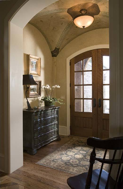 The foyer has an arched french front door and a groin vault ceiling mounted with a warm semi-flush light.