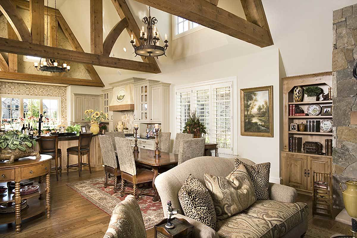 This open layout view shows the living room, dining area, and kitchen under the vaulted ceiling with exposed beams.