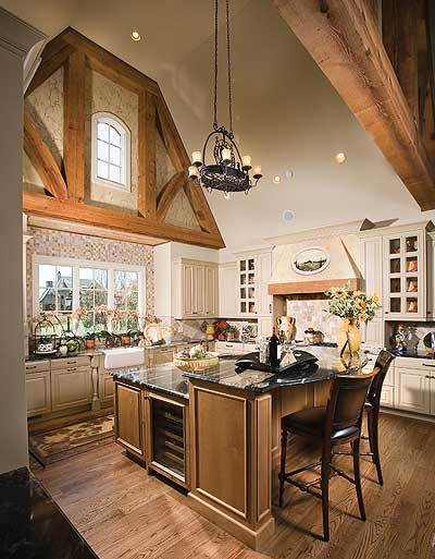 The kitchen is equipped with white cabinetry, a farmhouse sink, and a wine fridge fitted on the two-tier breakfast island.