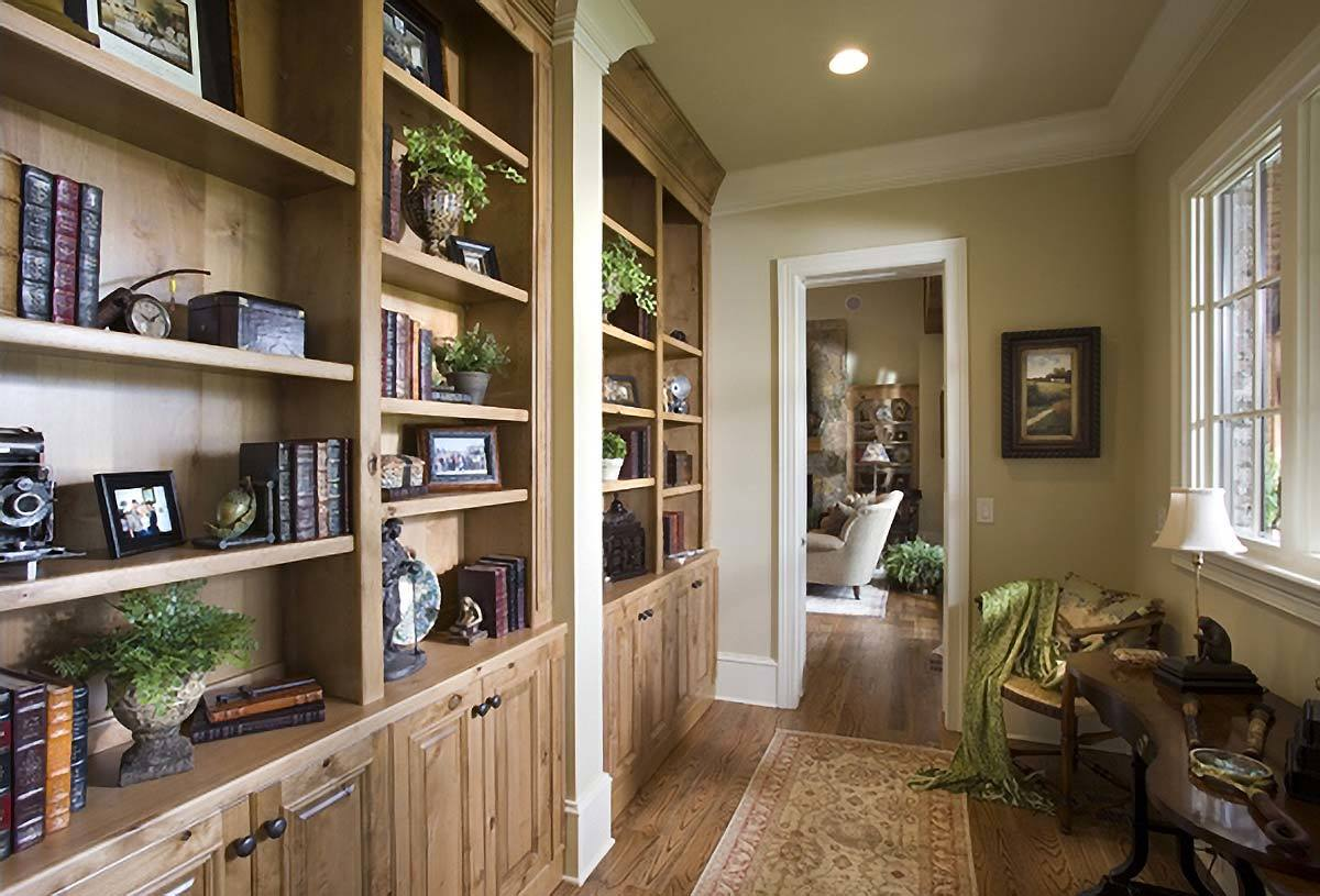 The study offers wooden furniture and a large built-in bookcase that blends in with the hardwood flooring.
