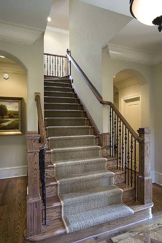 The traditional staircase has ornate wrought iron spindles and wooden steps topped with a classy carpet.