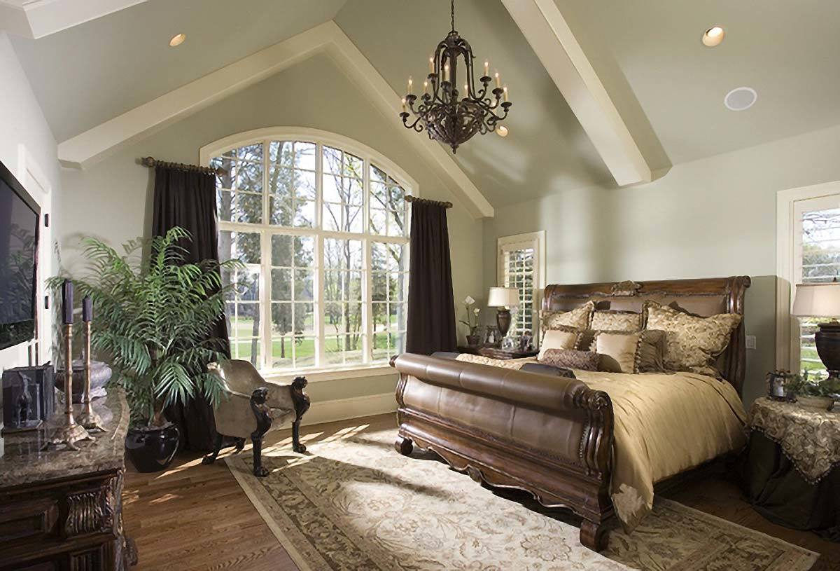 The primary bedroom features a large arched window and a cathedral ceiling lined with white decorative beams.