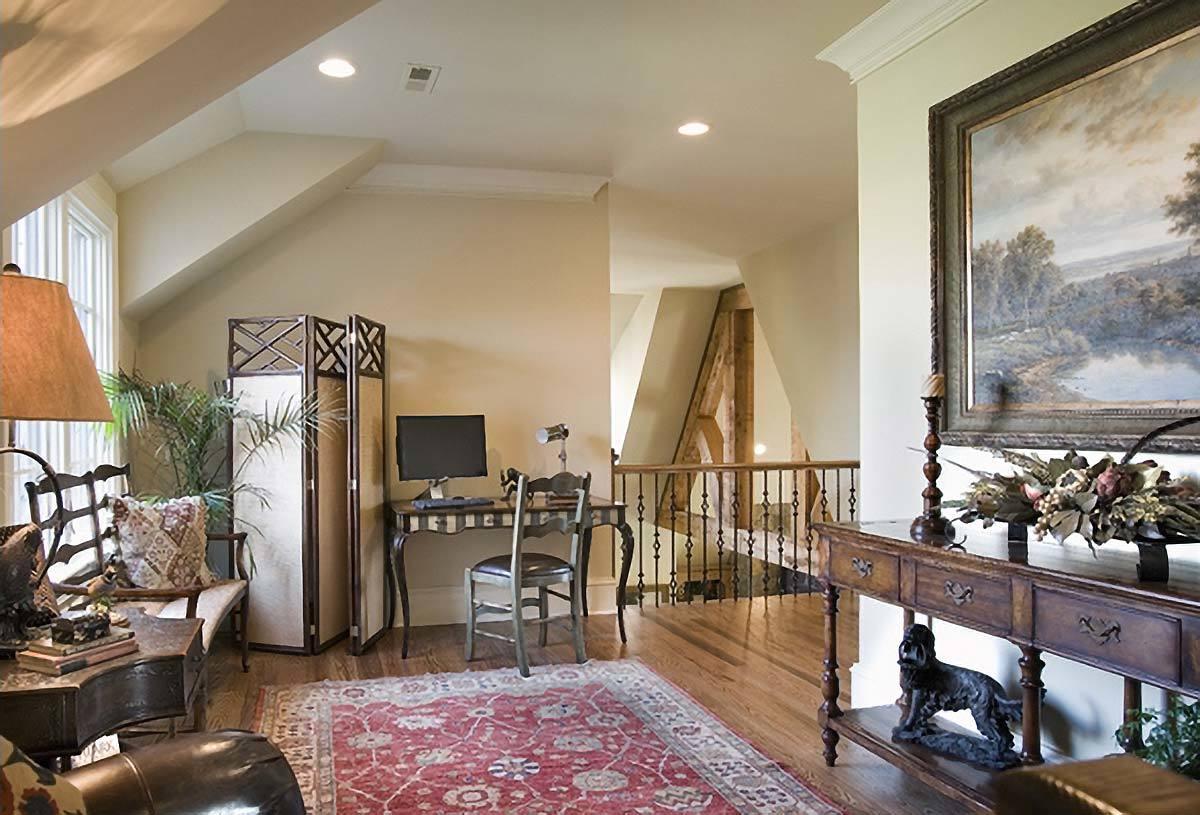 The loft is filled with dark wood furnishings and a vintage red area rug that lays on the hardwood flooring.