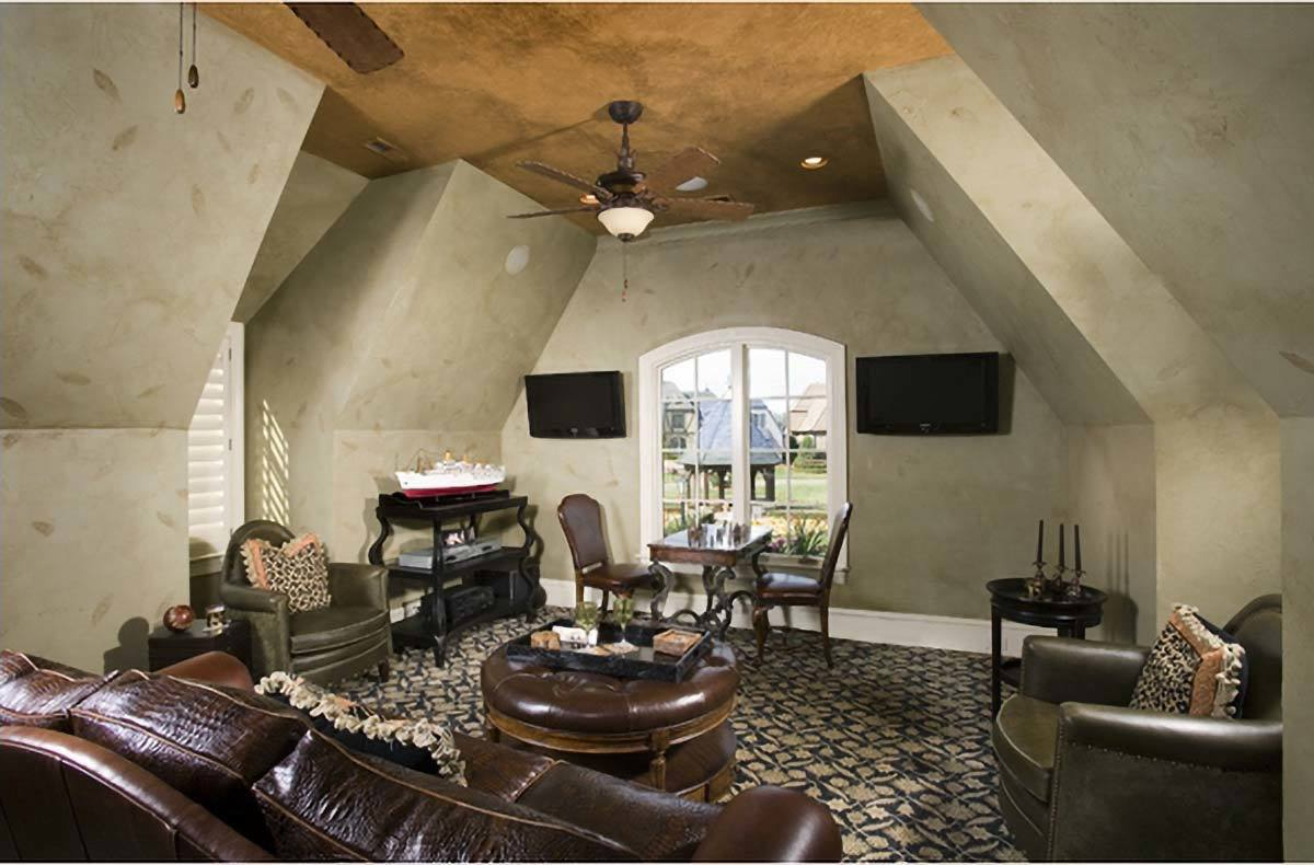 Recreation room with patterned carpet flooring and concrete vaulted walls mounted with a pair of flat-screen TVs.