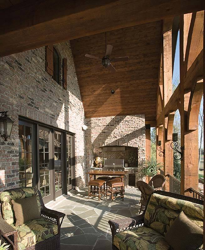 The covered patio has cushioned wicker seats, a wooden dining set, and a summer kitchen fixed against the stone brick walls.