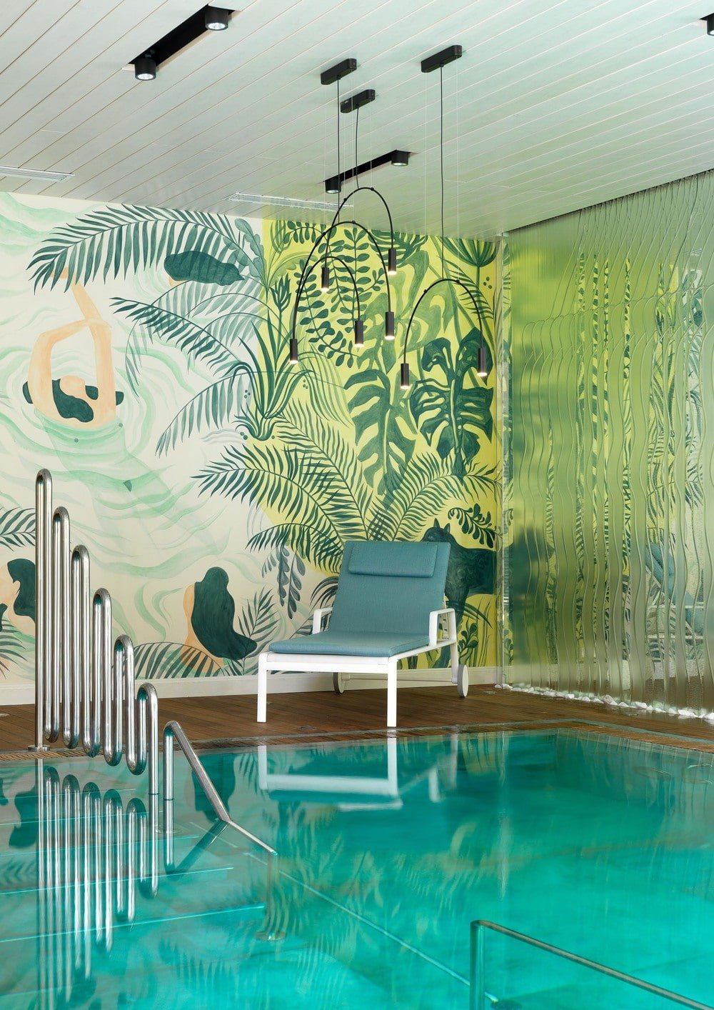 The walls of this indoor pool is filled with colorful murals that depict various tropical vegetation to set as a nice background for the gray cushioned lawn chair at the pool side.