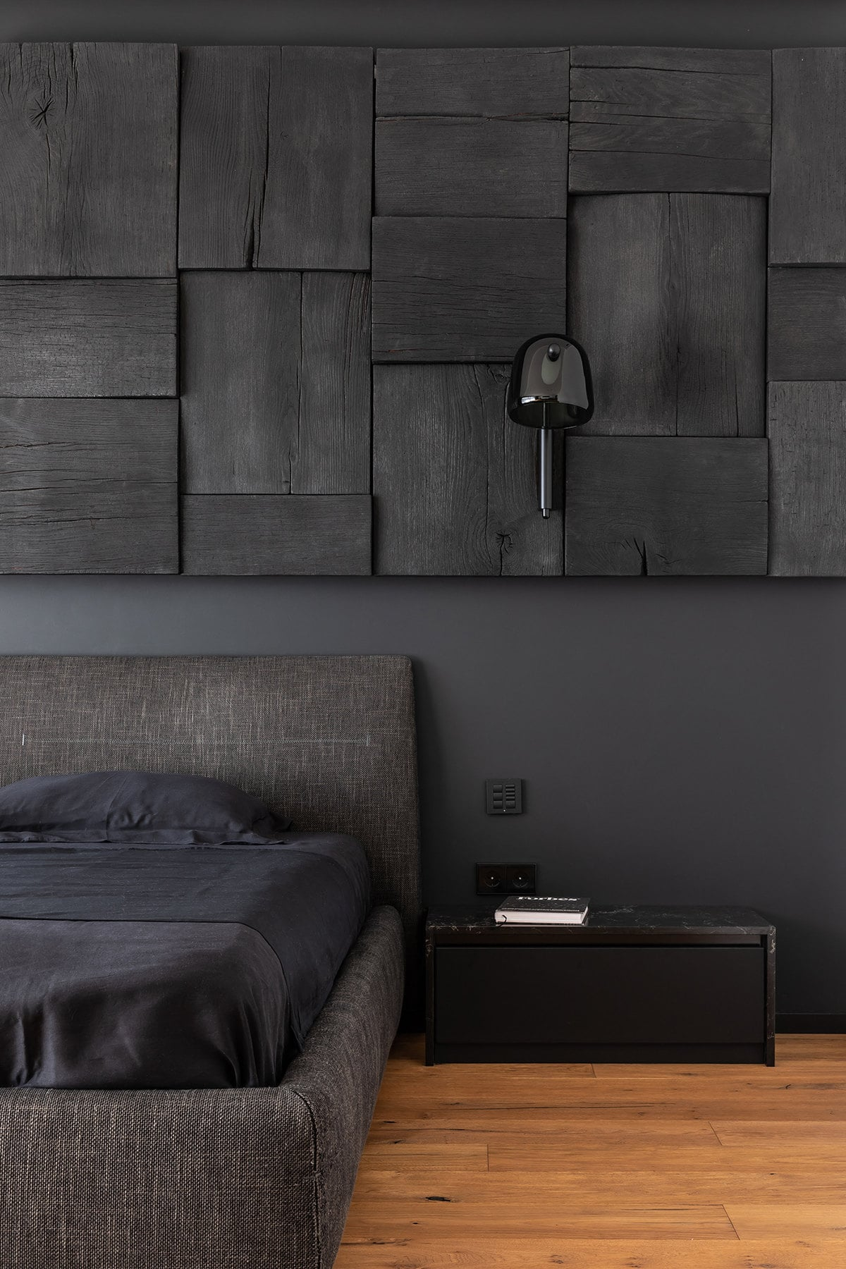 The black cushioned headboard of the bed is also flanked with small black bedside tables and has a matte black wall below the textured decorative black wall.