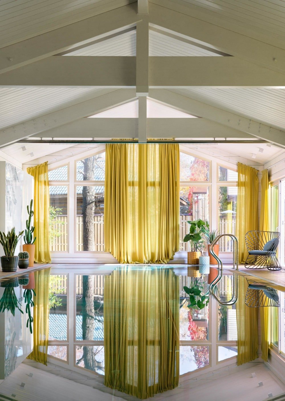 This house has a lush and luxurious indoor pool with a white cathedral ceiling that has exposed white beams complemented by the yellow curtains of the glass wall on the far side.