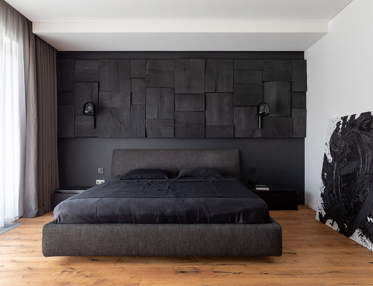 This is the gorgeous master bedroom with a large black platform bed with black sheets and pillows.