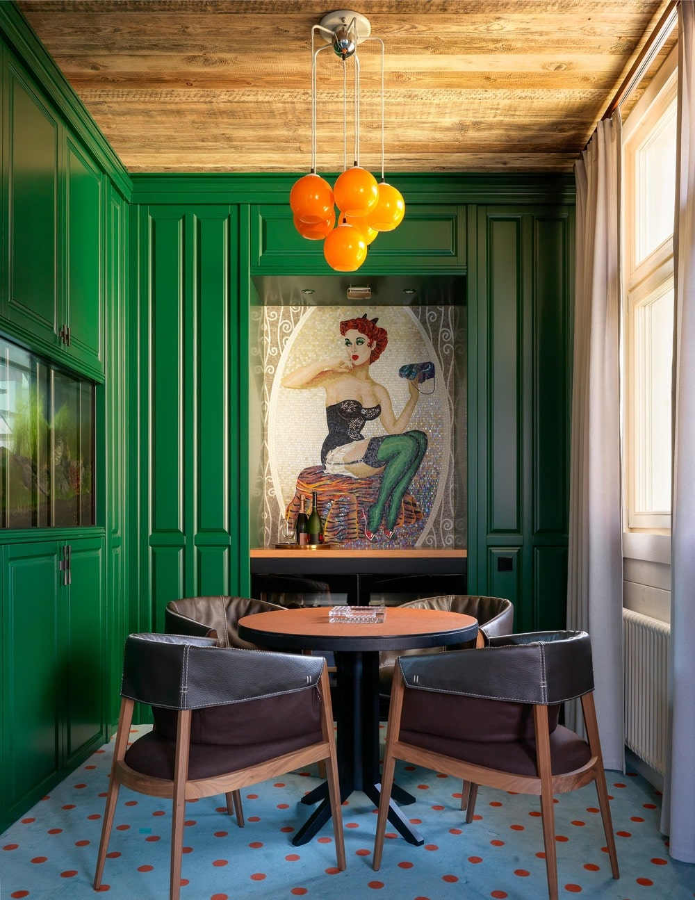 The game room has a small round table paired with comfortable wooden armchairs that is erfect for board games and card games. These are then adorned by the surrounding green walls contrasted by the colorful painting on the far wall.
