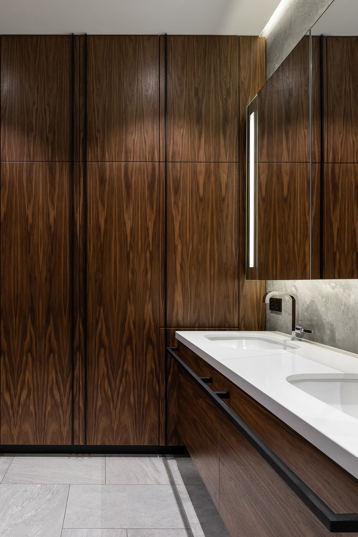 This bathroom has dark brown walls to match the tone of the vanity and its drawers. These are then contrasted by the bright white countertop with two sinks and topped with a large mirror.