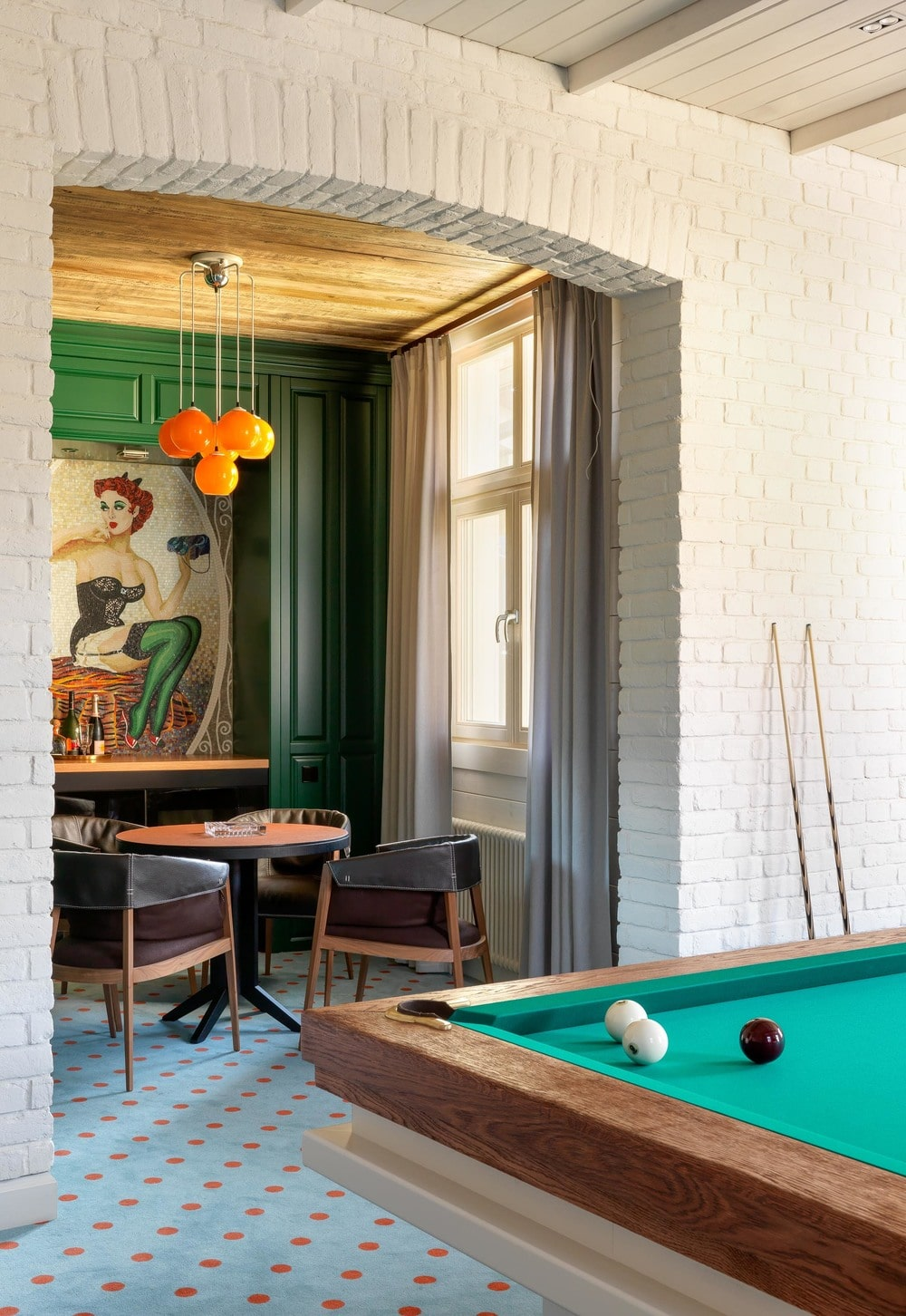 On the other side of the game table is the pool table illuminated by the natural lights coming in through windows. You can also see here the bright orange pendant lights hanging over the game table.