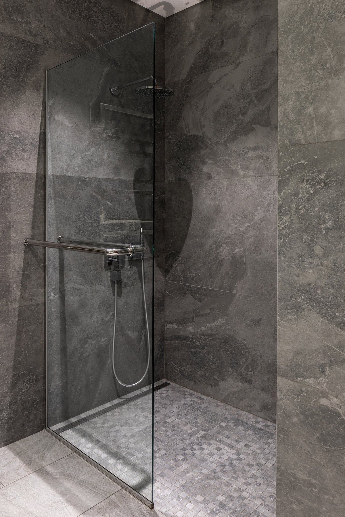 This is the glass-enclosed shower area with consistent gray tiles on its floor and walls.