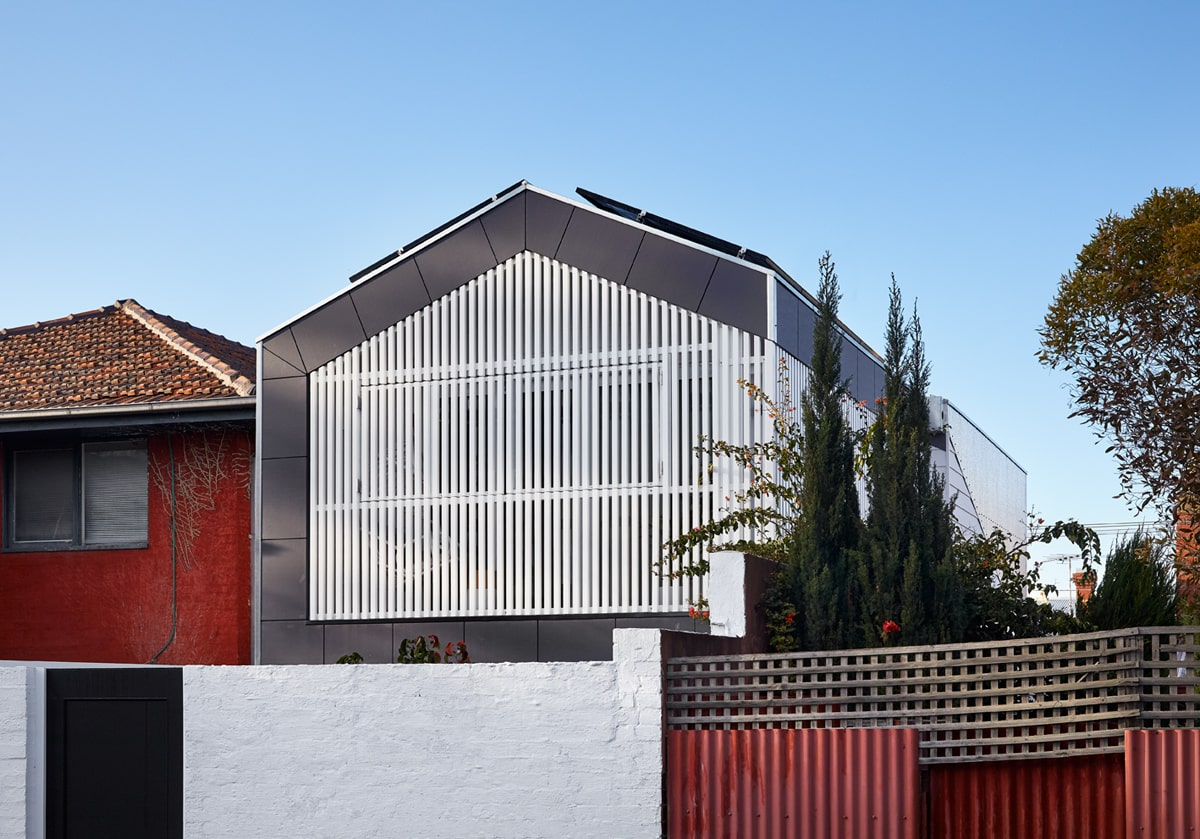 This is a view of the back of the house showcases the tall white concrete fence with a back gate with a contrasting black tone to it.