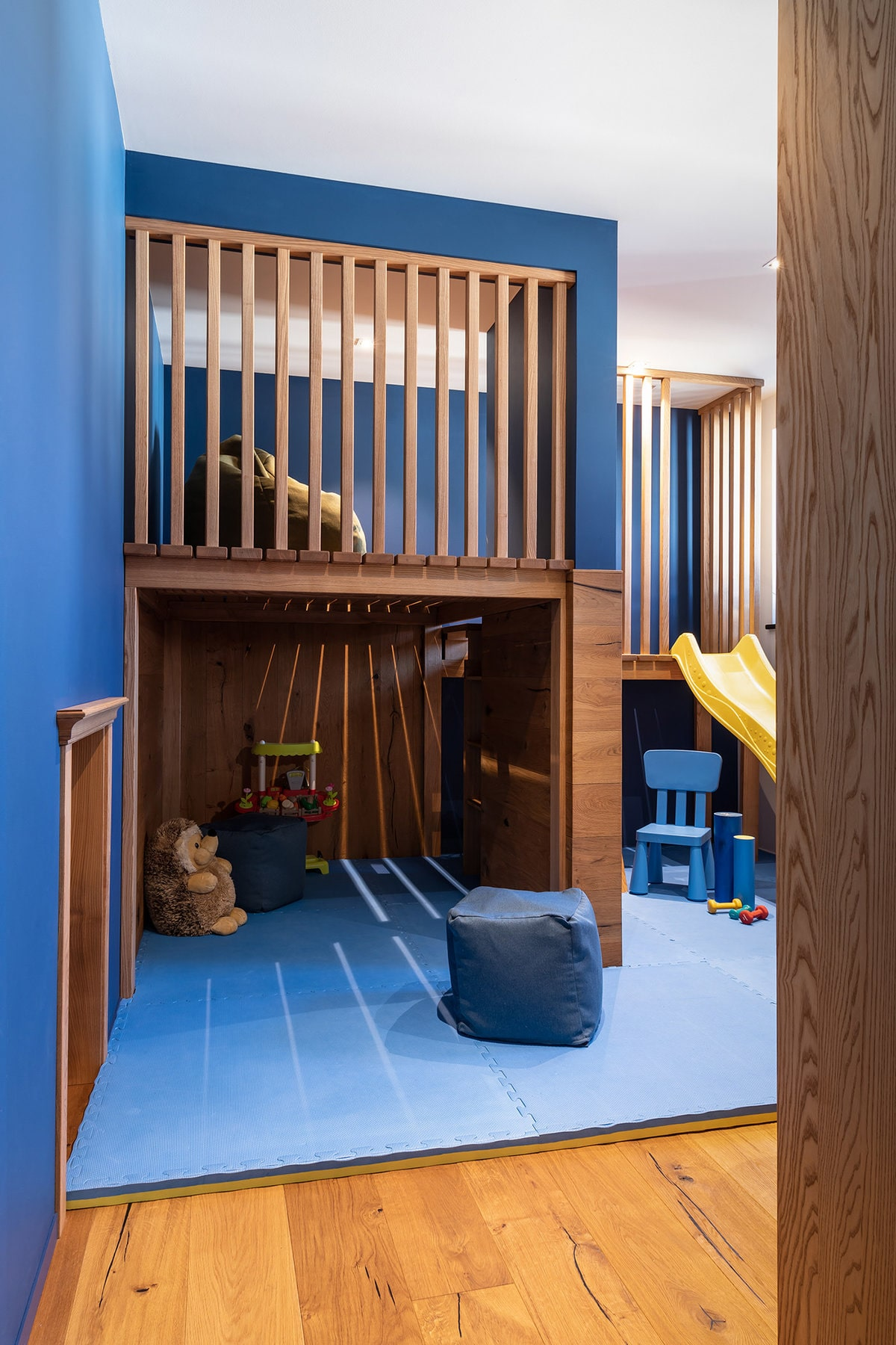 This is a charming playroom with a built-in playground made of wood contrasted by the brilliant blue walls.
