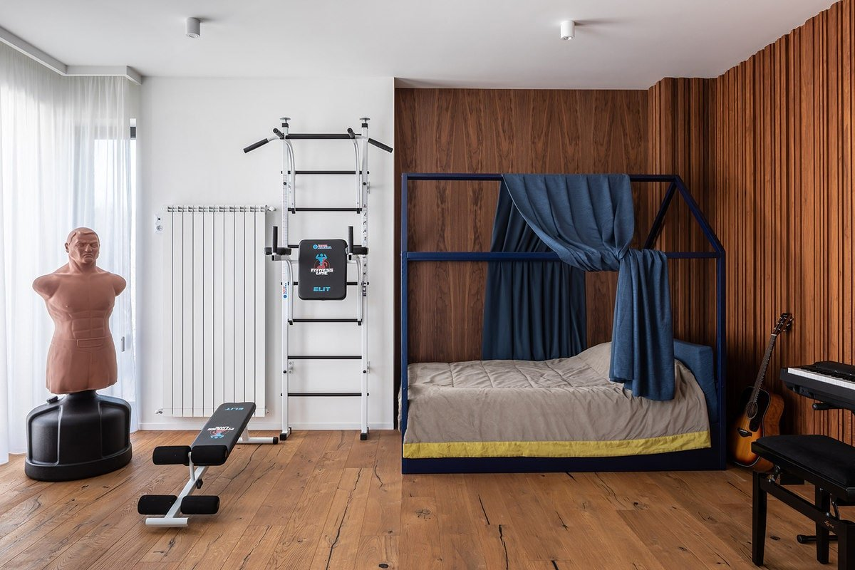 This bedroom has a four-poster bed that stands out against the wooden walls. These match perfectly with the hardwood flooring. There is also a small gym at the foot of the bed.