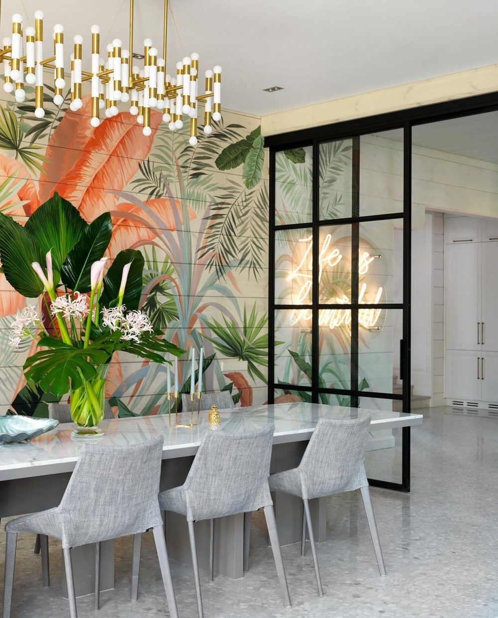 On the side of the wall mural is a glass wall that separates the dining area from the foyer. Here you can see the beautiful neon sign wall art on the white wall just beyond the glass wall.