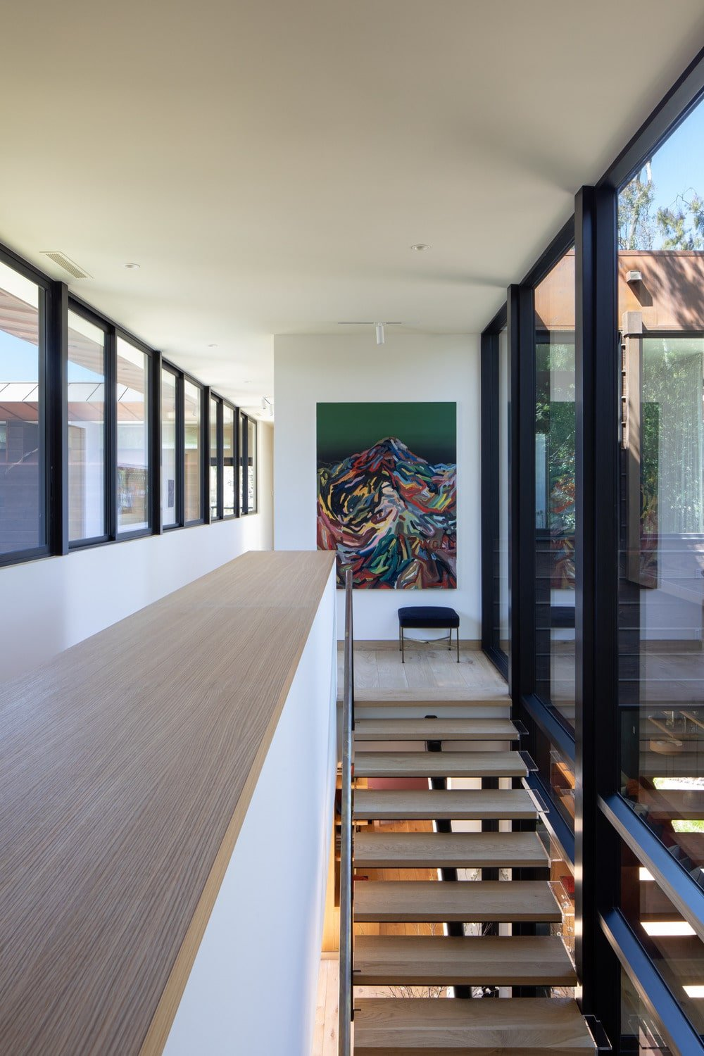 The second-floor landing has a gorgeous glass wall on one side and a row of windows on the other side to ensure that the area is constantly bathed in natural lighting.