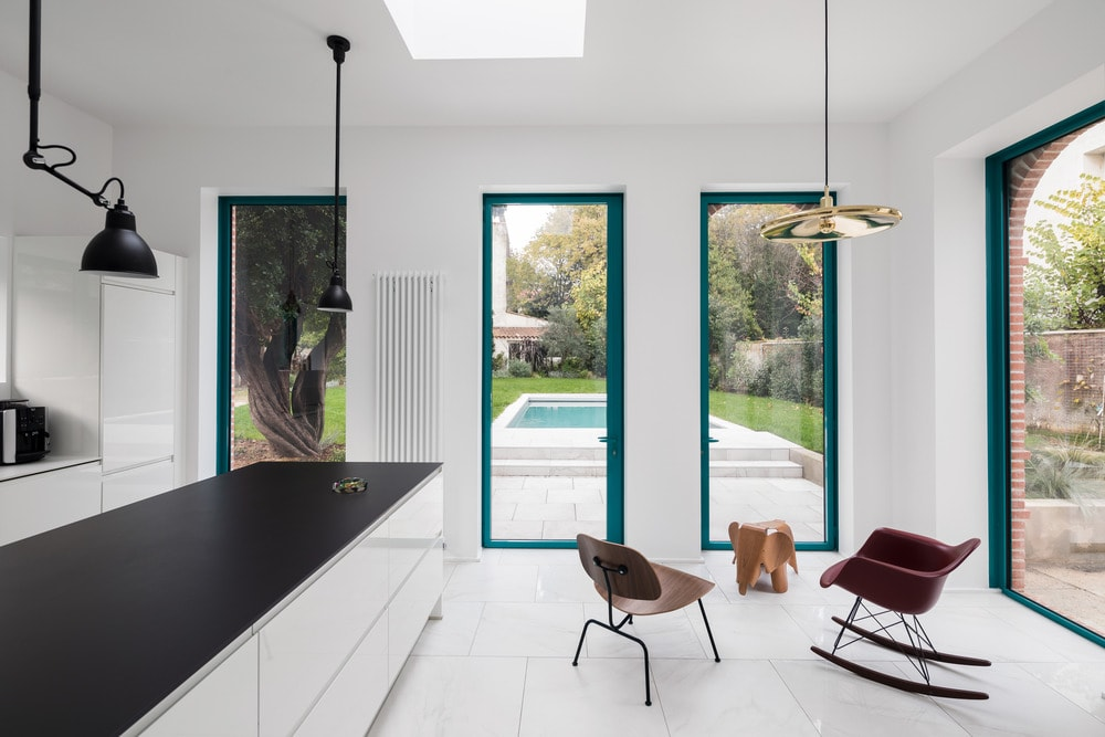 The interior has a bright white aesthetic with white walls, flooring tiles and the white ceiling that has a skylight.