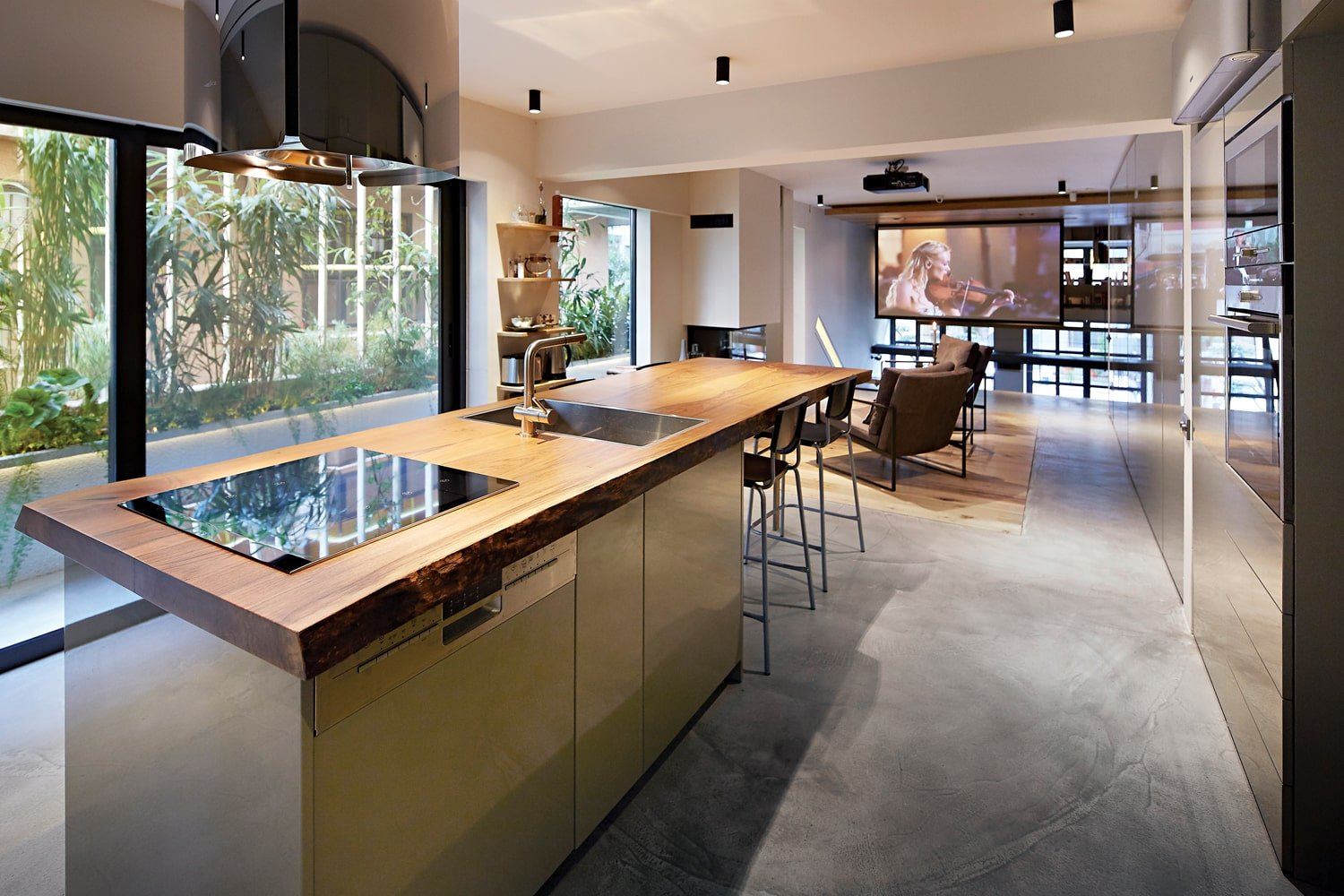 This large wooden countertop of the kicthen houses the modern glass-top stove and the sink topped with a white ceiling with modern lighting.