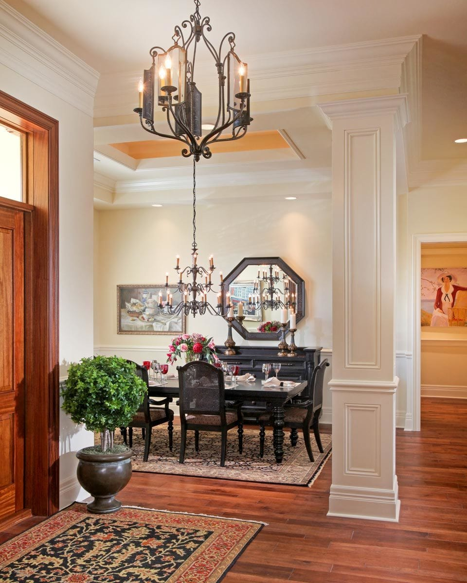 The dining room across the foyer offers black furnishings and a candle chandelier that hangs from the tray ceiling.