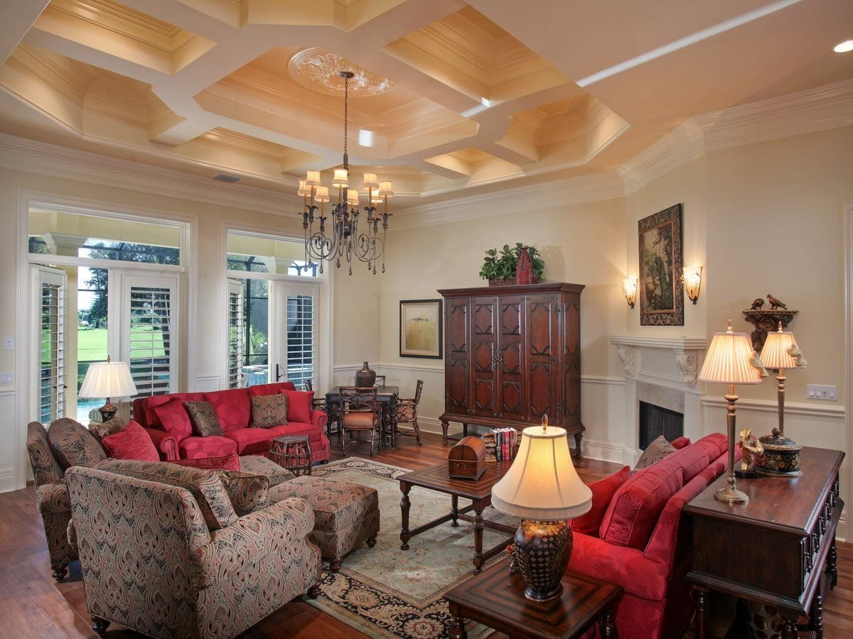 Living room with hardwood flooring, coffered tray ceiling, and two sets of french doors leading out to the lanai.