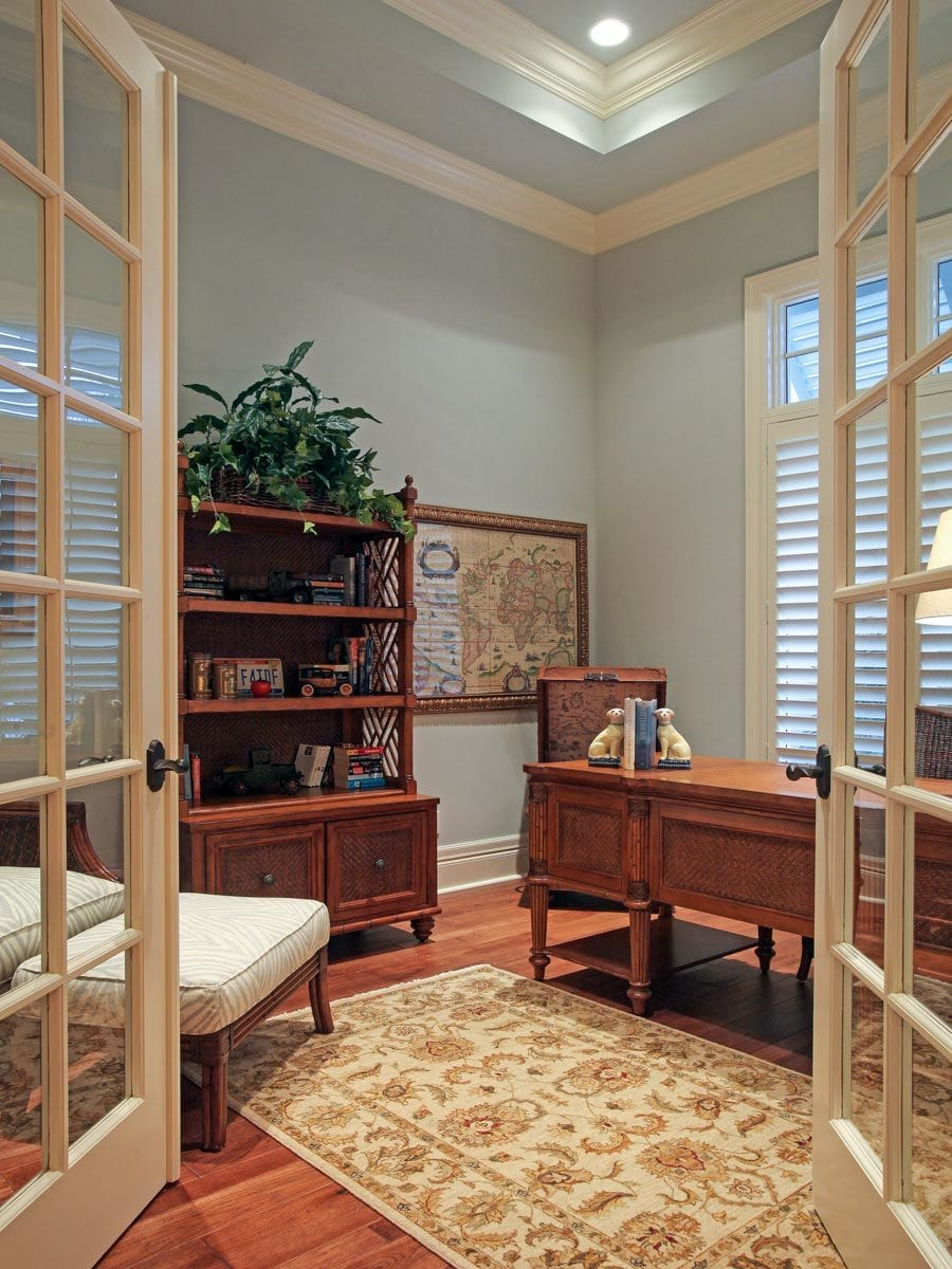 A french door opens to the study with a wooden desk and cabinets that blend in with the hardwood flooring.