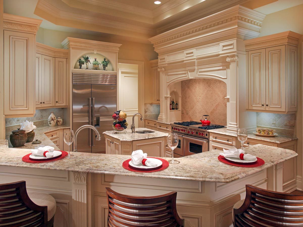 The kitchen offers a cooking alcove, cream cabinetry, a small center island, and a granite top peninsula with eating counter.