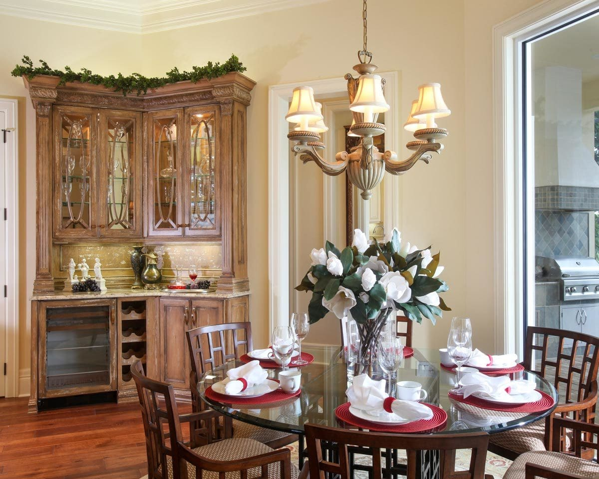 Breakfast nook with cushioned chairs and a round glass top table under the charming chandelier.
