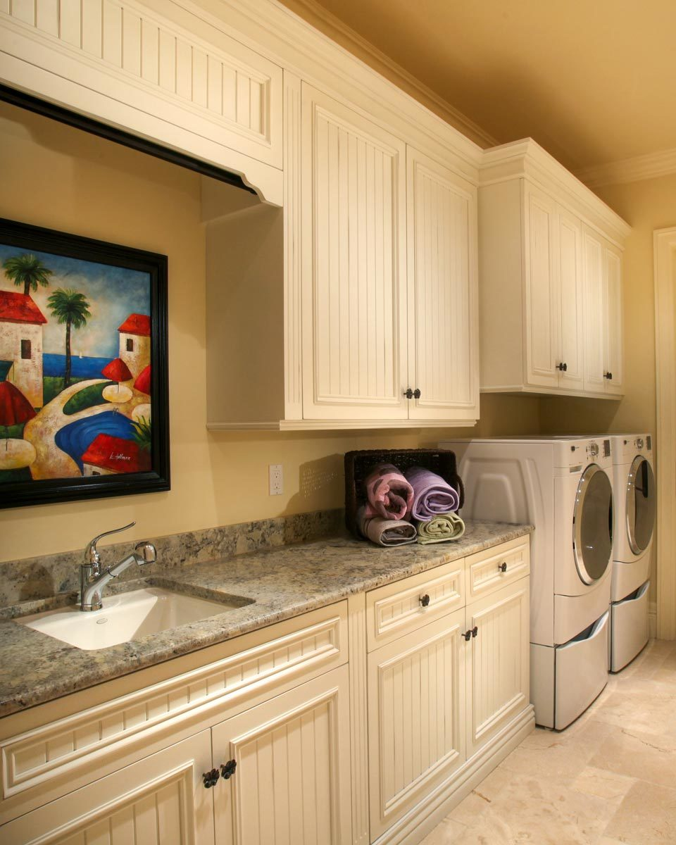 Utility room with white appliances, beadboard cabinets, and a granite countertop fitted with a porcelain sink.
