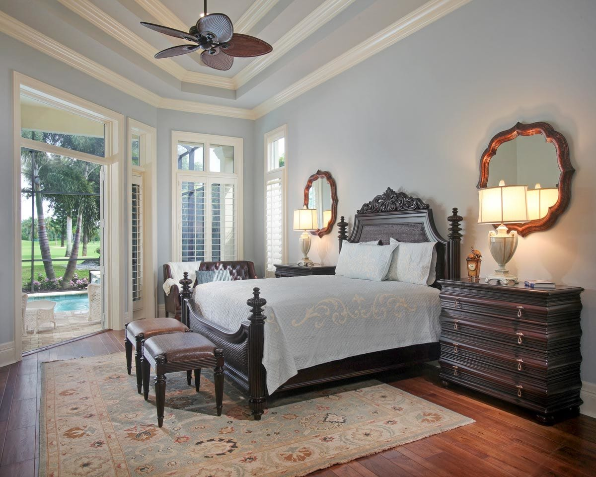 The master bedroom features a dark wood bed flanked by matching nightstands and mirrors.