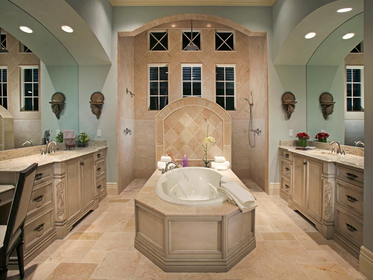 The master bathroom is equipped with a pair of sink vanities, a drop-in bathtub, and an open shower.