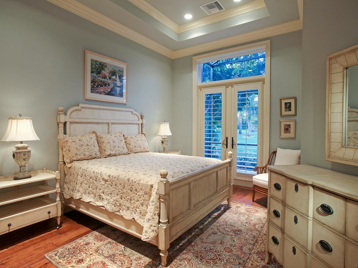 This bedroom has warm hardwood flooring, a tray ceiling, and light blue walls adorned with framed artworks.