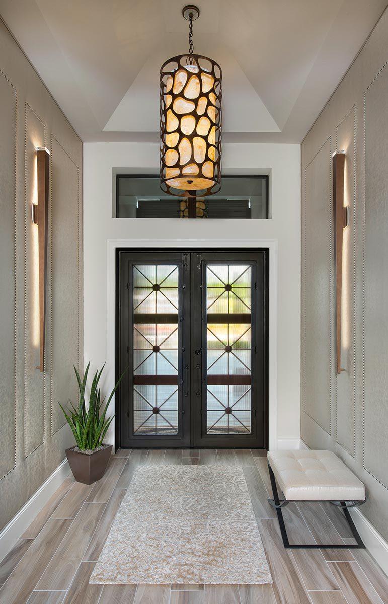 The foyer has a stylish french door, a tufted bench, and a classy rug illuminated by a large cylindrical chandelier.